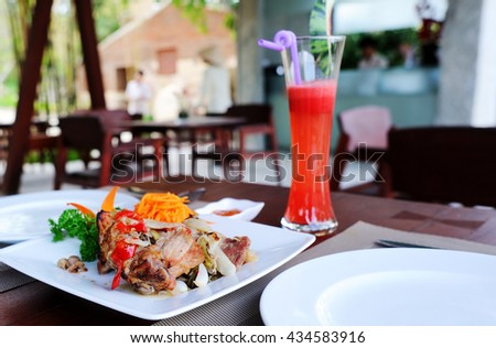 Natural light photo of dinner in the shore restaurant with watermelon juice - stock photo