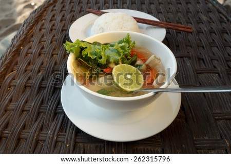 Natural light photo of lemongrass seafood soup with steamed rice, shallow DOF view 2 - stock photo