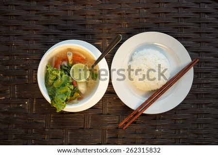 Natural light photo of lemongrass seafood soup with steamed rice, top view 2 - stock photo