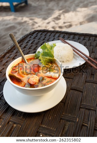 Natural light photo of Tom Yam seafood soup served with rice, shallow DOF seaside view 1 - stock photo