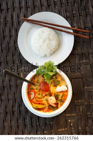 Natural light photo of Tom Yam seafood soup served with rice top view - stock photo