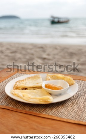 Natural light photo with shallow DOF of crepes with mango jam on mat and a wooden table with seaview backround - stock photo