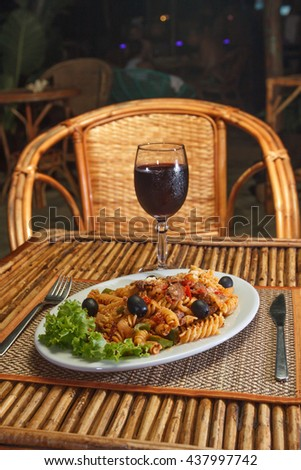 Natural light photo with shallow DOF of macaroni pasta with bolognese sauce and parmesan cheese on a white plate and glass of red wine - stock photo