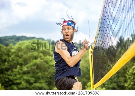 Natural looking beach volleyball player with stars and stripes bandana celebrates  his game success emotional. - stock photo