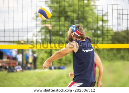 Natural looking beachvolley ball player with stars and stripes bandana plays forearm pass - stock photo
