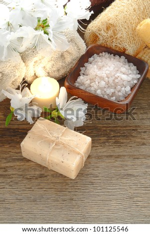 Natural Marseilles artisan aromatherapy facial and body care bath soap bar tied with organic raffia twine and bathing salts with flowers and towels on wood table in a holistic care and relaxation spa - stock photo
