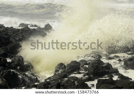 Natural metaphor of conflict: Ocean wave exploding against volcanic rocks along Pacific coast of Oregon - stock photo