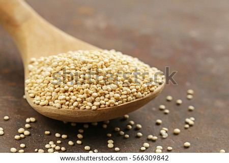 Natural organic cereal quinoa in a wooden spoon