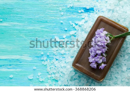 natural organic soap, and sea salt with flowers on a blue wooden table spa,  black soap out of tar - stock photo