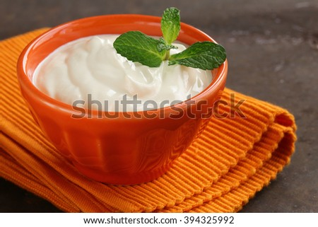 Natural organic sour cream in orange bowl - stock photo