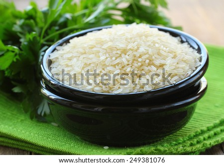 natural organic white rice in bowl on a wooden background - stock photo