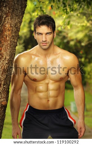 Natural portrait of a very fit male model outdoors - stock photo