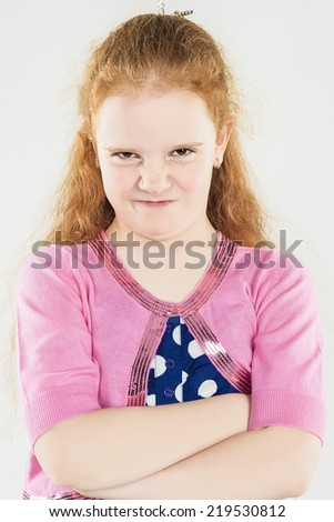 Natural Portrait of Caucasian Red-haired Angry Little Girl with Hands Folded. Standing Against White Background. Vertical Image Composition - stock photo