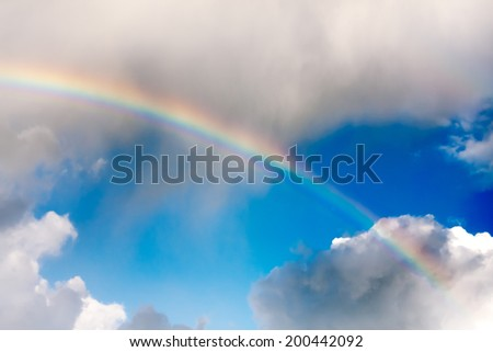 Natural rainbow over blue sky and white clouds - stock photo