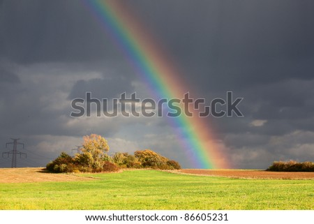 Natural rainbow over green field and dark sky - stock photo