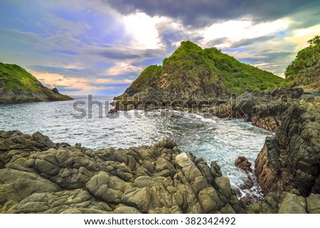 Natural rock with strong water wave and cloudy sunset background at Pantai Semeti Lombok, Indonesia - stock photo