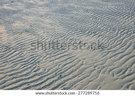 Natural sand pattern on  flat sandy beach during low tide. - stock photo