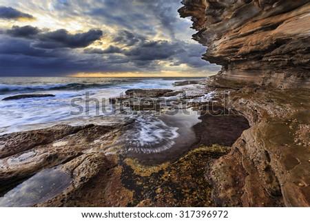 natural sandstone rocks forming high rising landscape at sea edge of coastal line in Sydney, Australia - stock photo