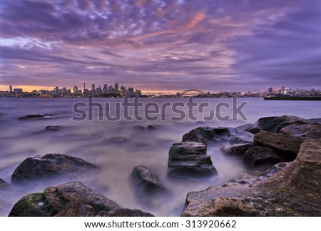 Natural seascape with distant Sydney city CBD landmarks across harbour at low tide during cloudy sunset - stock photo