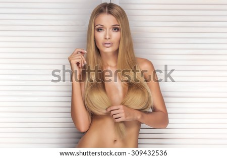 Natural sexy blonde woman with long healthy hair looking at camera, posing naked, covering breast.  - stock photo