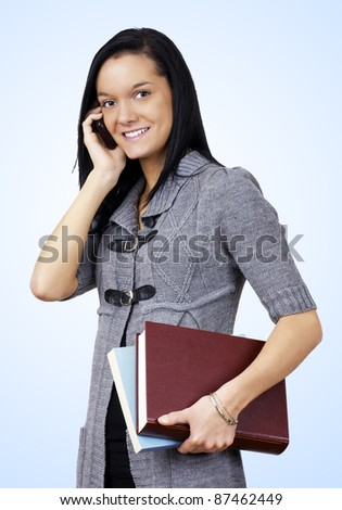 Natural smiling young woman student carrying books and taking on her cell phone over light blue gradient background - stock photo