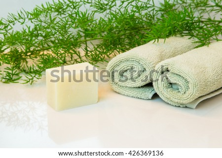 Natural soap or shampoo bar. Rolled green towels in a spa setting. Green plant decor in background. Bathroom white countertop.