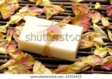 Natural soap with rose petals on bamboo mat - stock photo