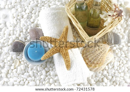 Natural spa elements-spa essentials and skin care items on white pebbles - stock photo