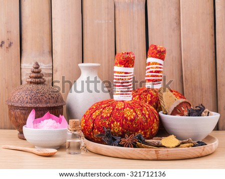 Natural Spa Ingredients herbal compress ball and essential Oil for alternative medicine and relaxation Thai Spa theme with bamboo background. - stock photo
