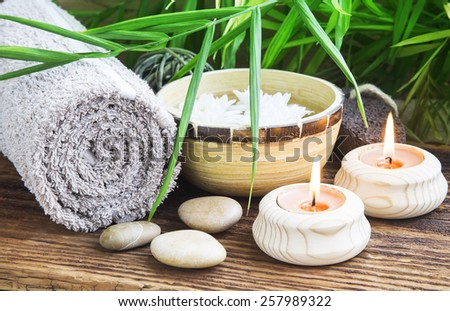 Natural Spa Setting with Green Leaves and Burning Candles, Towel and Rocks, Bamboo Bowl with Water on Wooden Background - stock photo