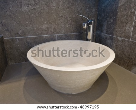 natural stone designer hand wash basin with chrome tap over - stock photo