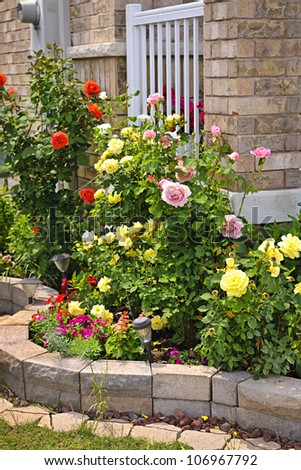 Natural stone landscaping in home rose garden - stock photo