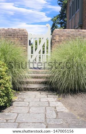 Natural Stone Path to Backyard Garden Gate with Brick Wall - stock photo