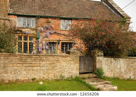 Natural Stone Village Manor House and garden with stone wall to the front and Wisteria growing up the wall
