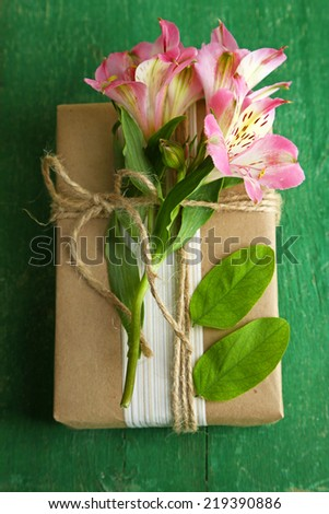 Natural style handcrafted gift box with fresh flowers and rustic twine, on wooden background - stock photo