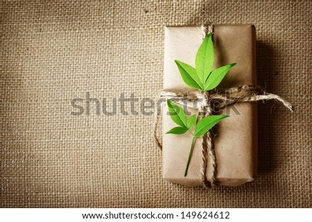 Natural style handcrafted gift box with rustic twine on burlap with copy space - stock photo