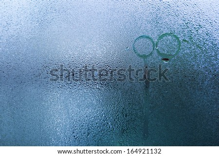 Natural water drop on glass with imprint of wedding rings - stock photo