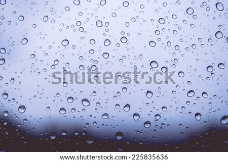 Natural water drops on blue window glass background - stock photo