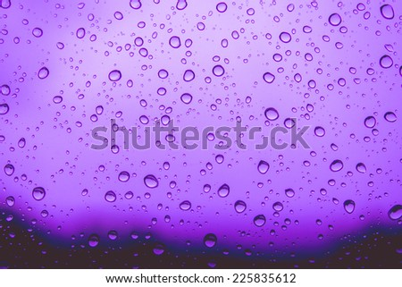 Natural water drops on  purple window glass background - stock photo