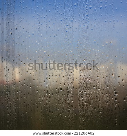 Natural water drops on window glass with city and nature background