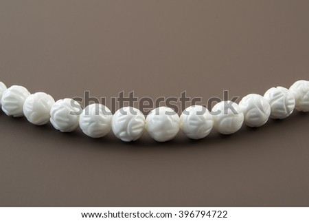 Natural white coral beads necklace on a brown background