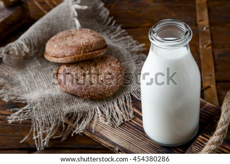 Natural whole milk in bottle and on old wooden background