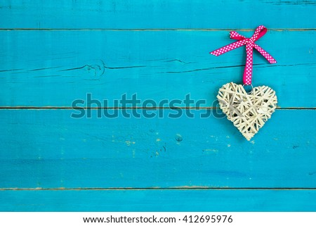 Natural wicker heart with pink polka dot ribbon hanging on antique rustic teal blue wood background - stock photo