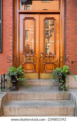 Natural Wood Double Front Doors with Inset Windows and Greenery  - stock photo