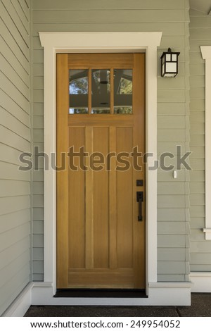 Natural Wood Front Door with Surrounding White Door Frame on Sage Green Exterior  - stock photo