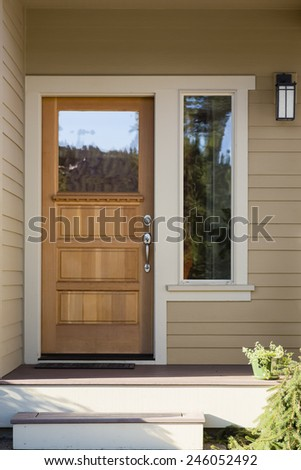 Natural Wood Front Door with Surrounding White Door Frame, Tan Siding, and Windows - stock photo