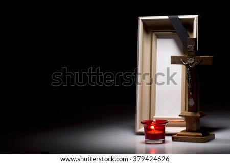 natural wooden mourning frame with candle and crucifix on dark background - stock photo