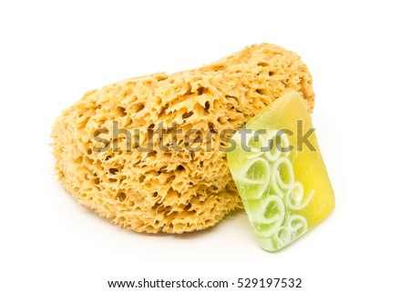 Natural yellow cleaning sponge with handmade soap bar over white background
