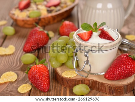 Natural yogurt with fruit on a brown background - stock photo