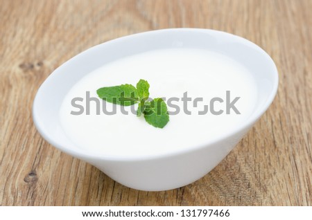 natural yogurt with mint leaf on a wooden table - stock photo